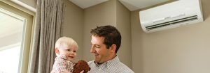 Dad and baby smiling at each other with ductless heat pump in background.