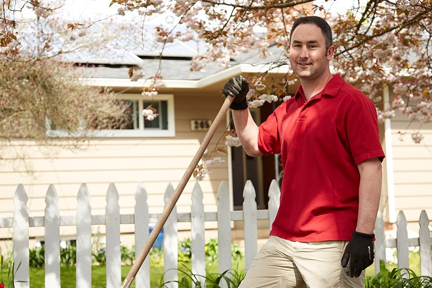 Man standing in front of his home with a rake in hand